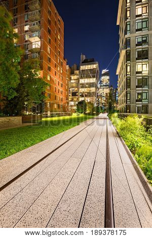 Highline promenade and old railway tracks at twilight with high-rises and building lights in Chelsea. Manhattan New York City