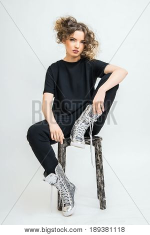 A smart girl is sitting on a chair in a fashionable suit. An excellent idea for advertising a female costume.