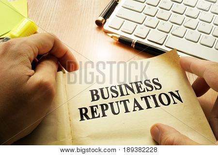 Hands holding documents with title Business Reputation.