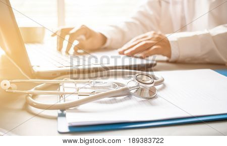 Medicine doctor's working on laptop computer and hand doctor on background. Focus on stethoscope