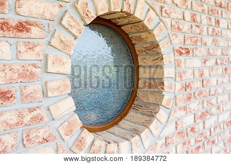 Round window on brick wall - shallow depth of field - focus on the closer arch of the window