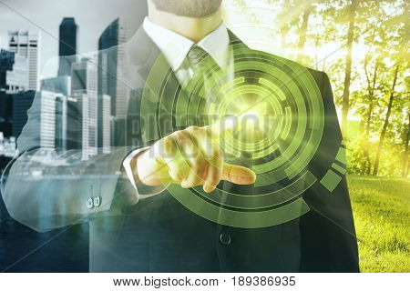 Businessperson pointing at abstract illuminated leaf icon on city background. Double exposure. Green business concept