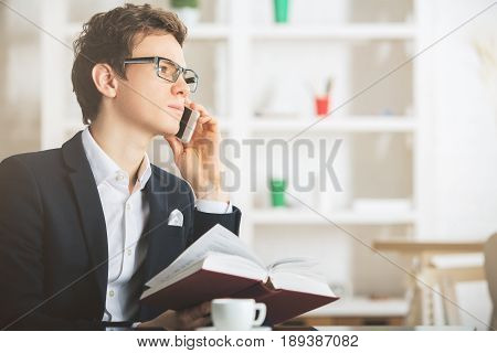 Man With Book Using Mobile Phone
