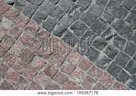 Rubble gray and brown square stones paved road with a diagonal border