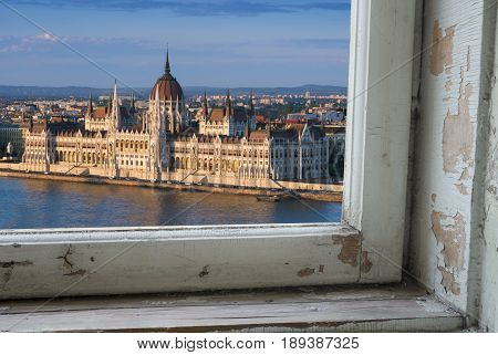 Looking through a castle window, the view of Buda in the foreground with the Hungarian Parliament building on the Pest side of Budapest in the background