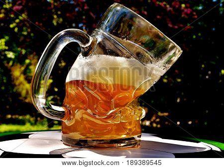 Beer with foam in a bent beer glass