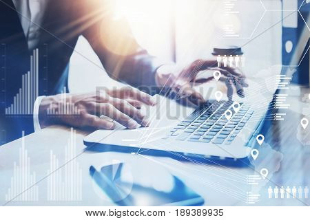 Concept of digital screen, virtual connection icon, diagram, graph interfaces.Businessman working at sunny office on laptop while sitting at the wooden table.Blurred background.Flares