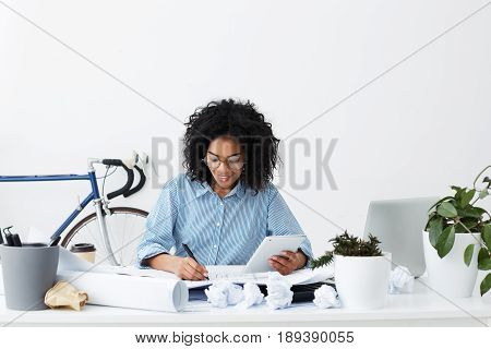 Portrait Of Experienced Professional Young Dark-skinned Woman Architect Holding Digital Tablet In On