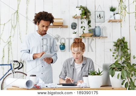 Stylish Afro American Young Male And Caucasian Female With Red Hair Making Presentation Together Usi