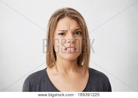 Close-up Portrait Of Unhappy Discontent Young Woman Having Trendy Hairdo Raising Eyebrows In Despair