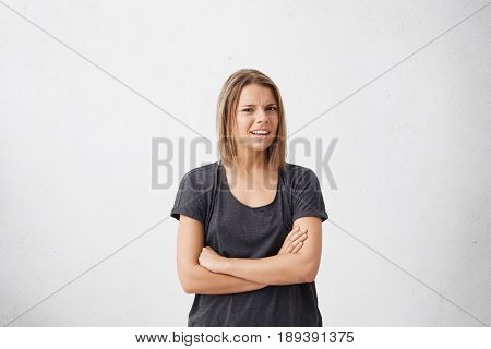 Studio Shot Of Attracive Doubtful And Dissatisfied Young Woman Having Skeptical And Suspicious Look,
