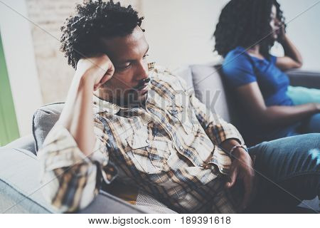 Young displeased black couple.Upset man being ignored by partner at home in the living room.American african men arguing with his stylish girlfriend, who is sitting on sofa couch next to him.Blurred.