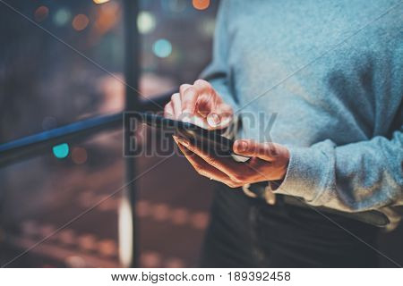 Closeup view of woman holding modern mobile phone in hands.Girl pointing fingers on empty touch mobile screen at night. Horizontal, blurred background, bokeh effects