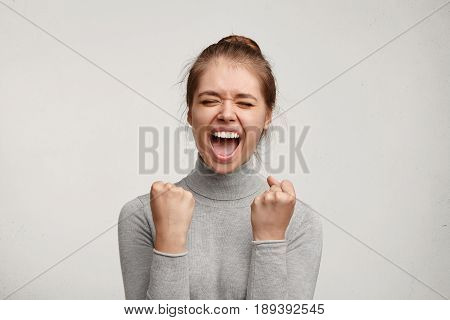 Cheering Happy Young Caucasian Female With Pure Skin And Beautiful Appearance Clenching Fists Being