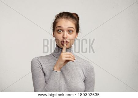 Studio Shot Of Wide Eyed Pretty Girl In Turtleneck Asking For Silence Or Secrecy, Holding Finger At