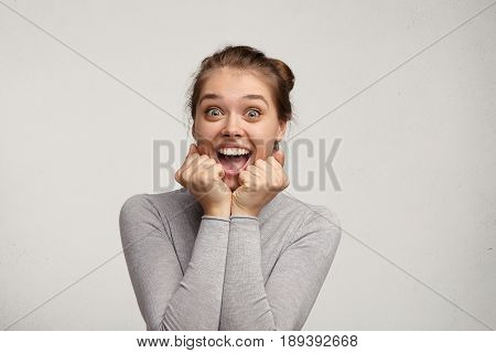 Portrait Of Emotional Positive European Teenage Girl Wearing Her Light Hair In Bun, Shouting In Amaz