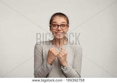 Excited Attractive Female Student Wearing Stylish Glasses Clenching Fists And Raising Eyebrows, Havi