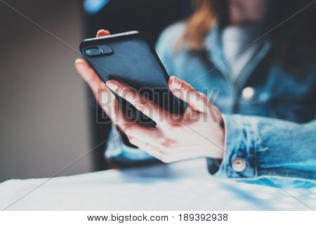 Closeup view of female hands holding modern mobile phone and pointing fingers on the touch screen.Horizontal, blurred background, bokeh effects