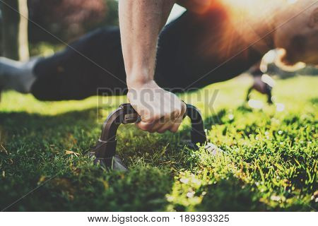 Closeup view of Handsome sport man doing pushups in the park on the sunny morning.Healthy lifestyle concept.Training outdoors.Blurred background.Visual effect.Horizontal