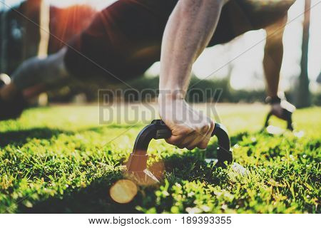 Closeup view of Handsome sport man doing pushups in the park on the sunny morning.Healthy lifestyle concept.Training outdoors.Blurred background.Flares effect.Horizontal