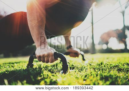 Healthy lifestyle concept.Training outdoors.Handsome sport man doing pushups in the park on the sunny morning. Blurred background. Horizontal closeup.Flares, sunlight effect