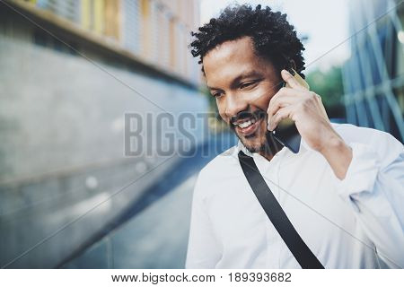Portrait of happy American African man using smartphone to call friends at sunny street.Concept of happy young people enjoying gadgets outdoors.Blurred background