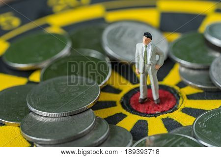 financial business concept as miniature business man standing at the center of dartboard with coins around.