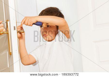 Portrait of little helper, six years old boy, fixing door handle using screwdriver at home