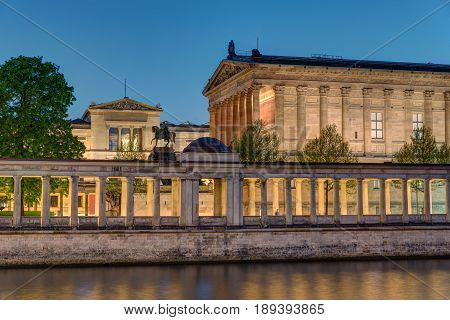 The Old National Gallery with the river Spree in Berlin at night