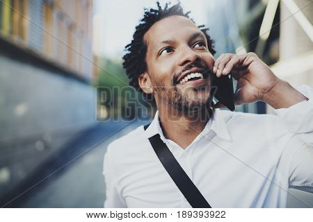 Portrait of happy American African black man using mobile phone to call friends at sunny street.Concept of happy young people enjoying gadgets outside.Blurred background