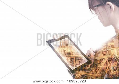 Double exposure of Engineer or Technician women with safety helmet operated platform or plant by using tablet with offshore oil and gas platform background for oil and gas business concept.