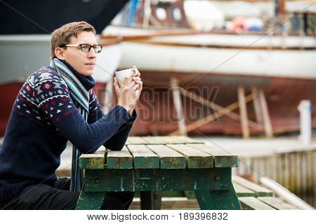Yachtsman with coffee sitting on a pier on a background of yachts