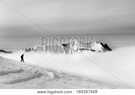 Black And White Silhouette Of Snowboarder On Off-piste Slope With Newly Fallen Snow And Mountains In