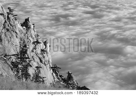 Black And White View Of Sunlit Cliffs And Sea In Clouds