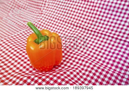 Orange Bell Pepper against red and white chequered cloth