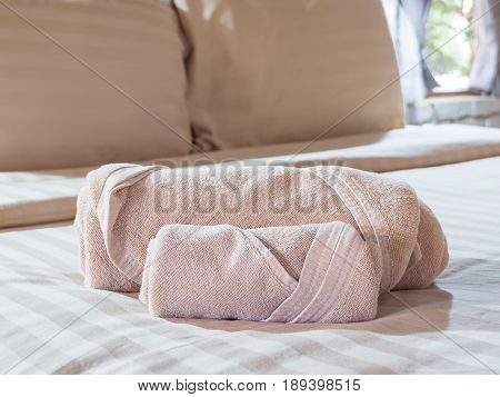 Two brownish color towels on bed decoration in bedroom interior with sunlight (Selective focus)