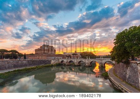 Saint Angel castle and bridge with mirror reflection in Tiber River during gorgeous dawn in Rome, Italy.