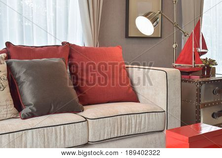 Classic Industrial Look Living Room With Beige Sofa And Red And Deep Brown Linen Pillows With Brass
