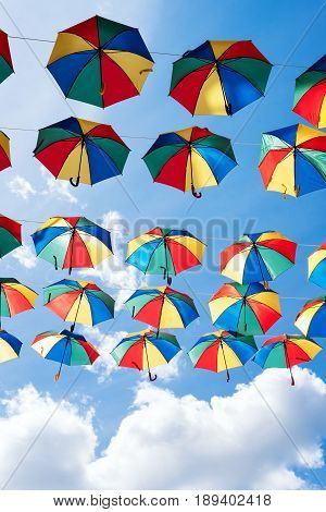 Colorful umbrellas background. Coloruful umbrellas urban street decoration. Hanging Multicoloured umbrellas over blue sky.