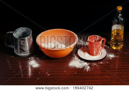 Orange cup measuring cup and a steel sieve sunflower oil stand on a wooden table on a black background. Flour.