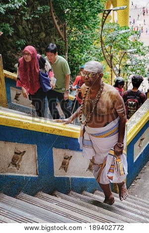 Batu Caves, Malaysia - February 7, 2016: Malaysian Hindu man in traditional dress walks up the steps to the Batu Caves. The cave is one of the most popular Hindu shrines outside India