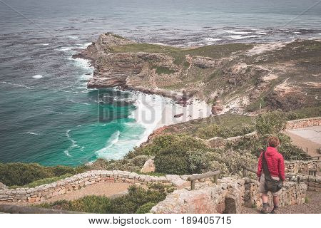 Tourist Hiking At Cape Point, Looking At View Of Cape Of Good Hope And Dias Beach, Travel Destinatio