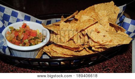 Chips and tortilla dip  Chips in a basket tray with nacho dips in a small bowl with blue and white checkered napkin