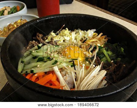 Bibimbap with raw egg and sesame in a hot stone pot  Bibimbap is a traditional Korean favorite made up of steamed rice, topped with meat, raw egg, mushrooms, and vegetables and usually served in a hot stone pot.