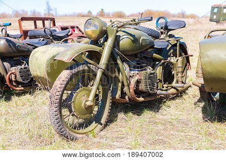 Samara Russia - April 30 2017: Russian vintage rusty motorcircle at the field in sunny day. Soviet military retro motorcycle