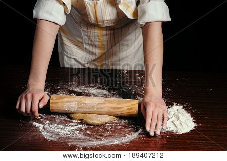 A woman in the kitchen is rolling a dough on a wooden table with a wooden rolling pin.