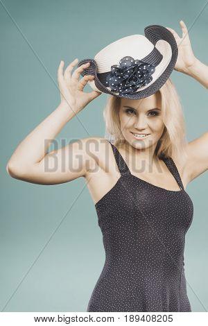 Woman Wearing Short Navy Dress Holding Sun Hat