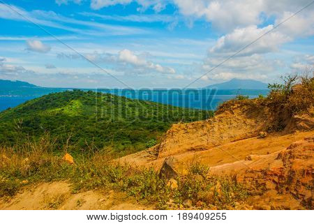 Green Hills, Sand, Water And The Mountain On The Horizon. Luzon Island. Philippines