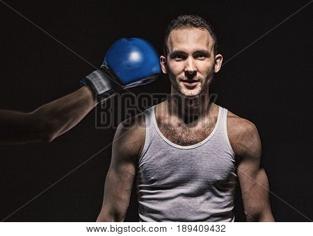 Boxing glove near the man's face on black background