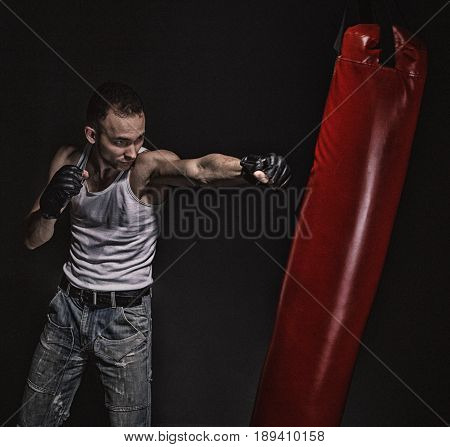 Boxing kick in the red boxing bag on black background